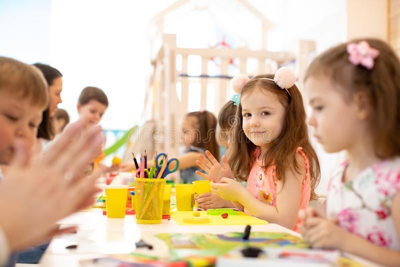 kindergarten-kids-doing-arts-crafts-teacher-day-care-centre-children-148142355